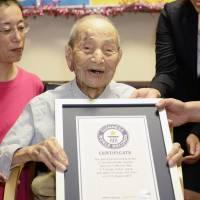 Yasutaro Koide, 112, holds a Guinness World Records certificate recognizing him as the world's oldest man last August in Nagoya. He died Tuesday. | KYODO