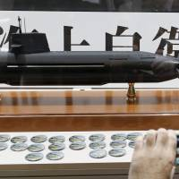 A visitor takes a picture of a model of a Japan Maritime Self-Defense Force diesel-electric Soryu submarine at the MAST Asia 2015 defense exhibition and conference in Yokohama in May. | REUTERS