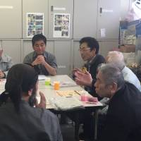 Members of Oyaji no Kai share their experiences about taking care of elderly family members at its monthly meeting in Arakawa Ward, Tokyo, on Nov. 13. | MIZUHO AOKI