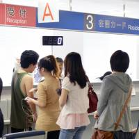 People line up at the Tokyo Immigration Bureau for residence cards.  | KYODO