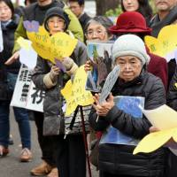 "Supporters holding portraits of former ""comfort women"" rally in front of the Foreign Ministry on Wednesday. 