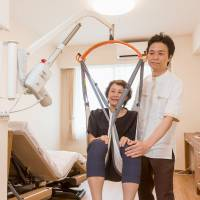 Swing Lift CoCoRo, developed jointly by Orix Living Corp. and Moritoh Co., lifts a woman using an arm capable of making a 360-degree turn. | ORIX LIVING / KYODO