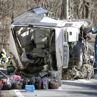Investigators on Friday examine the gnarled remains of a bus that crashed on a mountain road in Nagano Prefecture earlier that day. | KYODO