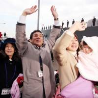 A family waves as the Maritime Self-Defense Force destroyer Murasame leaves its home port in Yokosuka, Kanagawa Prefecture, in January 2008. | BLOOMBERG NEWS