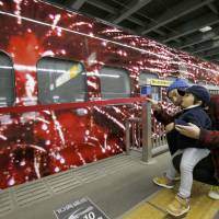 A father and son admire the Genbi Shinkansen, a specially decorated six-car bullet train, at JR Omiya Station in Saitama on Tuesday. | KYODO