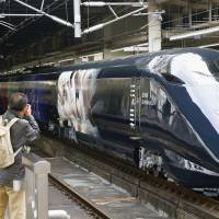 Bystanders snap photos of the Genbi Shinkansen, a bullet train adorned with images of fireworks, at JR Omiya Station. Officials hope it will promote tourism to Niigata. | KYODO