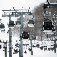 Skiers ascend the slopes in Kutchan, Hokkaido, last February. The ski industry in Japan, already hurt by the country's aging population, is suffering from balmy winter weather. | BLOOMBERG