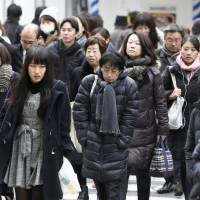 Pedestrians brave the cold Saturday in the Umeda district of Osaka. | KYODO