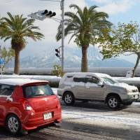 Cars are capped with snow in the city of Kagoshima on Monday. | KYODO