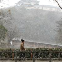 A pedestrian walks in snow in front of Wakayama Castle in the city of Wakayama on Sunday afternoon. | KYODO