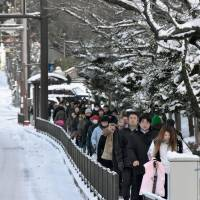 Commuters crowd a sidewalk Monday in the city of Nagasaki as buses and trams were shut down by the snow. | KYODO
