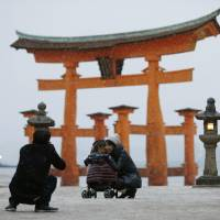 A family takes a snapshot Sunday afternoon in front of the famous Otorii gate at Itsukushima Shrine after snow fell in Hatsukaichi, Hiroshima Prefecture. | KYODO