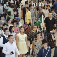A file photo shows travelers arrive at Narita airport near Tokyo last August. | KYODO