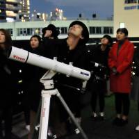 People participate in a stargazing session in late November on a deck above hoshicafe SPICA in Osaka. | KYODO
