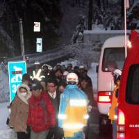 People evacuate a spa resort in Matsumoto, Nagano Prefecture, on Saturday after being stranded for about a day after trees knocked down by heavy snow blocked routes to the area. | KYODO