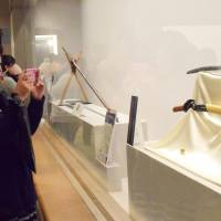 A woman takes a picture of the legendary sword Heshikiri Hasebe diplayed at Fukuoka City Museum on Jan. 11. | KYODO