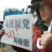 A protester near the Takahama nuclear plant on Friday holds a placard denouncing the restart. | KYODO