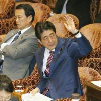 Prime Minister Shinzo Abe raises his hand to answer a question during a Lower House committee meeting on Wednesday. | KYODO
