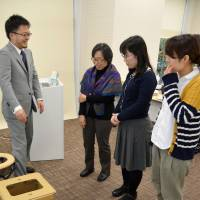 Participants listen to an explanation about various kinds of emergency lavatories during a seminar held by research center Japan Toilet Labo in Tokyo on Dec. 19. | KYODO