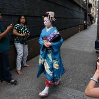 Tourists snap photographs of a maiko, or apprentice geisha, walking through the Gion area of Kyoto in May. | BLOOMBERG
