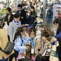 Travelers returning from their New Year's holidays crowd the arrival lobby at Haneda Airport in Tokyo on Sunday. | KYODO