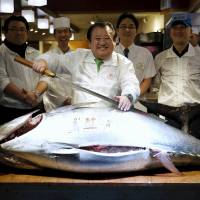 Kiyomura Co. President Kiyoshi Kimura, who runs a chain of sushi restaurants, poses with a sword and a 200-kg bluefin tuna at his sushi restaurant outside the Tsukiji fish market in Tokyo on Tuesday. | REUTERS