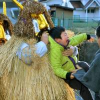 Young men dressed as Namahage demons scare a child during a traditional year-end ritual in Oga, Akita Prefecture, on Thursday, the last day of 2015. | KYODO