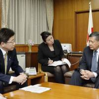 U.N. special rapporteur on North Korea Marzuki Darusman (right) talks with Katsunobu Kato, state minister in charge of the abduction issue (left), on Monday at the Cabinet Office in Tokyo. | KYODO