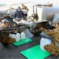 Self-Defense Forces troops supply drinking water to residents of Omuta, Fukuoka Prefecture, on Wednesday. Water pipes in the area have frozen, cutting the supply. | KYODO