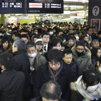 Stranded passengers throng JR Shinjuku Station in Tokyo on Monday morning as transportation services throughout the region were disrupted by snow. | KYODO