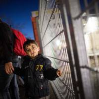 A Syrian asylum seeker and his son stand at the fence of the State Office of Health and Social Affairs (LAGeSo) registration center in Berlin on Dec. 21. | DPA / AFP-JIJI