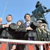 Left to right: Defense Minister Gen Nakatani, Deputy Prime Minister Taro Aso and Prime Minister Shinzo Abe attend a Maritime Self-Defense Force fleet review in October off the coast of Kanagawa Prefecture. | KYODO