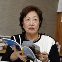 Ayako Sono peruses a copy of National Geographic. The former government adviser praised South Africa's apartheid system in a column in the Sankei Shimbun in February. | KYODO