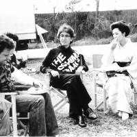 "Nagisa Oshima sits with producer Jeremy Thomas and Akiko Koyama during filming for ""Merry Christmas, Mr. Lawrence"" in Rarotonga in August 1982. 
