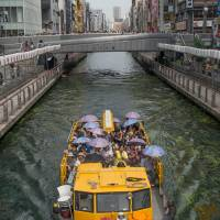 A cruise boat plies the murky waters of Dotonbori canal. | STEPHEN MANSFIELD