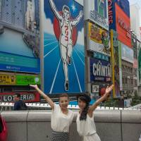 In the running for fun: Visitors pose on Ebisu Bridge before the iconic Glico Man sign. | STEPHEN MANSFIELD
