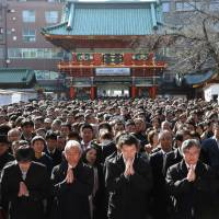 Pray for fortune: People pray on Jan. 4, the first business day of the year, at Kanda Myojin Shrine in Tokyo. However, will 2016 bring some of these workers a better work-life balance? | BLOOMBERG