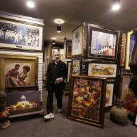 Toney Hughes, general manager of Sherwood Forest Art Gallery on Livernois Avenue, walks through the showroom in Detroit.   AP