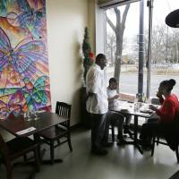 Heartbeat of the city: Don Studvent, chef and proprietor of 1917 American Bistro, chats with customers in his restaurant on Livernois Avenue in Detroit.   AP