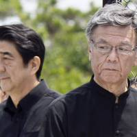 History lessons: Prime Minister Shinzo Abe and Okinawa Gov. Takeshi Onaga pay their respects at the Cornerstone of Peace in Itoman city on June 23 last year, the 70th anniversary of the end of the Battle of Okinawa. | KYODO