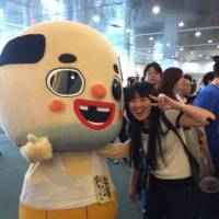 Azusa Matsuda, Society for the Promotion of Japanese Animation's director of industry relations poses with the Japanese character Chitchai Ossan at an Anime Expo. | UPRIGHT