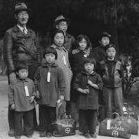 Grave Injustice:  Members of the Mochida family awaiting an evacuation bus in Hayward, California, May, 1942. ID tags were used to aid in keeping the family unit intact during all phases of the evacuation. | WIKICOMMONS