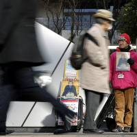 Unequal outcomes: A formerly homeless man sells The Big Issue on a street in Tokyo as office workers pass by. Japan feels less like an equal society than it used to. | BLOOMBERG