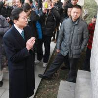 Sorrow: Hatoyama offers a prayer in front of a monument bearing the names of victims at the Nanjing Massacre Memorial Hall in 2013. | LIU JIANHUA NJ — IMAGINECHINA / AP