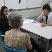 Stimulating patience: Christine Benson (left) and Ann Endo play a mother and daughter during a consultation with a Jikei University student. The Simulated Patients program aims to prepare medical students for dealing with foreign patients. | LOUISE GEORGE KITTAKA