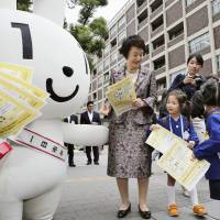 Bring out the big guns: Maina-chan the mascot and Yokohama Mayor Fumiko Hayashi spread the word about the My Number system in the Kanagawa prefectural capital in October. | KYODO