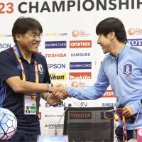 Japan manager Makoto Teguramori (left) and Shin Tae-yong, his South Korean counterpart, lead their teams into the Asian Under-23 Championship on Saturday in Doha. | KYODO