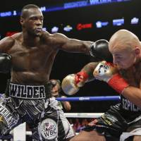 Deontay Wilder lands a punch on Poland's Artur Szpilka during their WBC heavyweight title fight in New York on Saturday. | AP