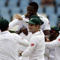 South Africa bowler Kagiso Rabada (top) celebrates with teammates after dismissing England's batsman Jonathan Bairstow for 14 runs on the fifth day of the fourth test match against England in Centurion, South Africa, on Tuesday. | AP