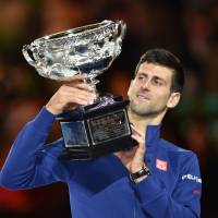 Novak Djokovic holds the Australian Open winner's trophy after beating Andy Murray in straight sets in Sunday's final in Melbourne. | AFP-JIJI